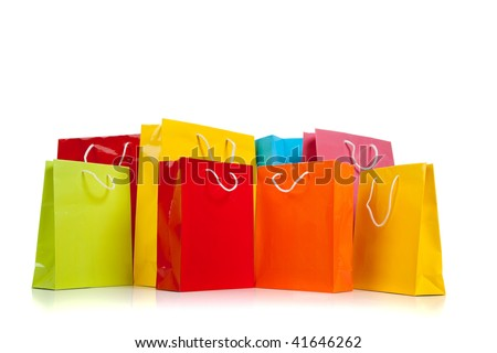 Assorted colored shopping bags including red, yellow, lime green, orange, pink and blue on a white background - stock photo
