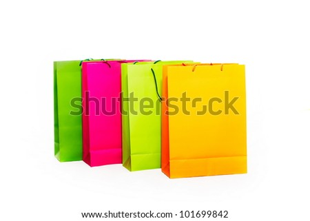 Assorted colored shopping bags including yellow, orange, pink and green on a white background