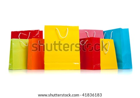 Assorted colored shopping bags including yellow, orange, red, pink, blue and green on a white background - stock photo
