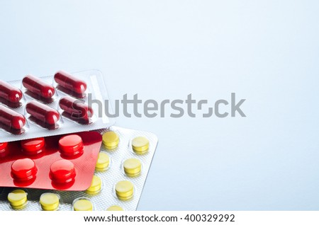 Assorted colorful pills and capsules in a Blister packaging on a light background close up, horizontal, copy space, selective focus, medical concept. - stock photo