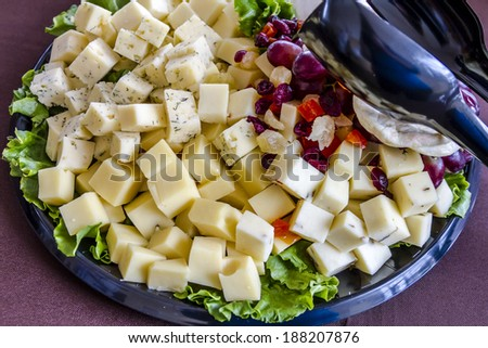 Assorted cubes of cheese, dried and fresh fruit siting on black tray - stock photo