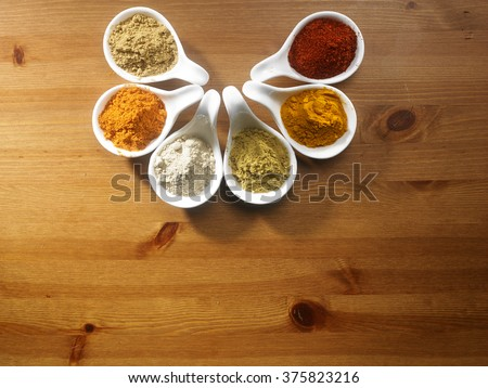 assorted curry powder in saucers on the wooden background - stock photo