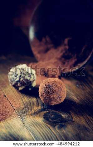 Assorted dark chocolate truffles on a dessert plate on dark wooden background vintage toned