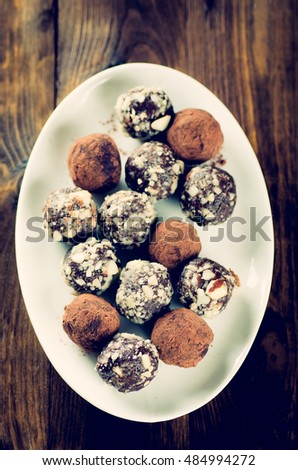 Assorted dark chocolate truffles on a dessert plate vintage toned
