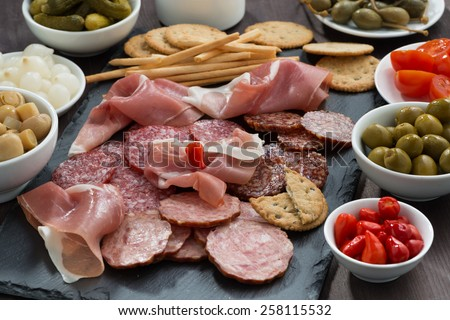 Assorted deli meat snacks, sausages and pickles on a blackboard, horizontal - stock photo