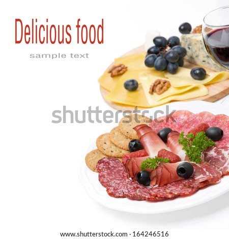 assorted deli meats, plate of cheese and a glass of wine, isolated on white - stock photo