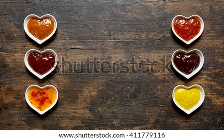 Assorted dips and sauces in a double banner with spicy chili, ketchup, chutney and mustard to serve as side dishes to a meal, rustic wood background with copy sapce