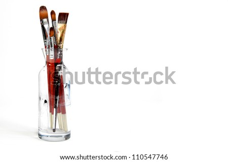 Assorted dirty old painting brushes in a glass flask. background - stock photo