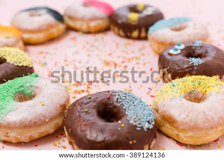 Assorted donuts on a pastel pink background, copyspace