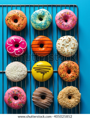 Assorted donuts with different fillings on blue background - stock photo