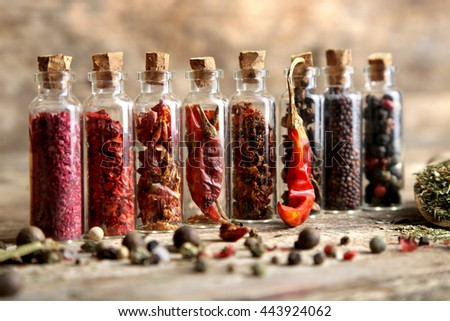 Assorted dry spices in glass bottles on wooden background - stock photo
