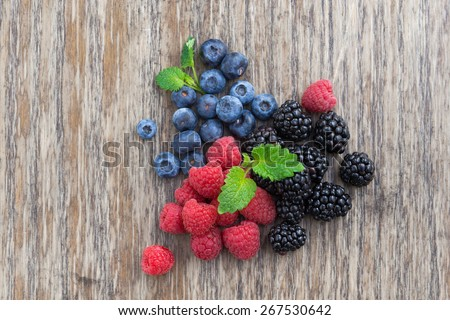 Assorted fresh berries on the wooden background, top view, horizontal - stock photo