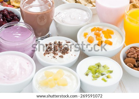 Assorted fresh fruit yoghurts and breakfast ingredients, close-up, horizontal - stock photo