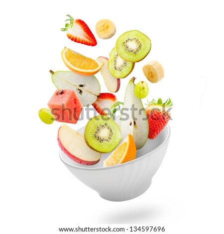 Assorted fresh fruits flying in a bowl/ Light salad with flying fresh fruits
