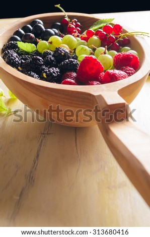 Assorted fresh garden berries on a wooden background, space for text, close-up. Raspberry, black currant, red currant, gooseberry, blackberry. - stock photo