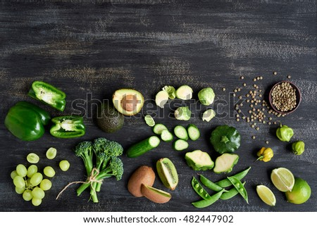 Assorted fresh green vegetables on dark rustic distressed background, broccolini, beans, capsicum, peppers, peas, brussels sprouts, kiwi, cucumber part of produce collection