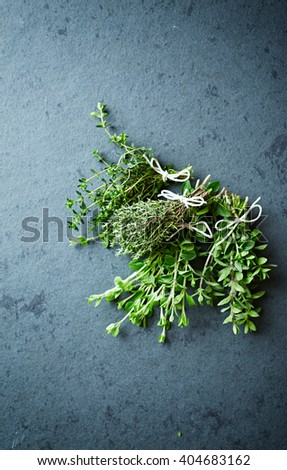 Assorted fresh herbs on a stone background - stock photo