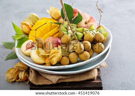 Assorted fresh ripe tropical fruits on a plate including mango, longan, kiwi and gooseberries - stock photo