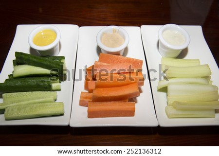 Assorted fresh vegetables (celery, cucumber and carrot) and  sauce - stock photo