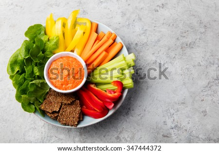 Assorted fresh vegetables with dip Healthy eating Roasted pepper sauce, spread Stone background - stock photo