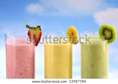 Assorted fruit and berry smoothies on blue sky background - stock photo