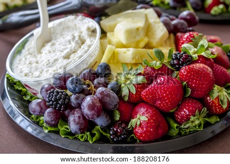Assorted fruit tray with strawberries, blueberries, grapes, pineapple, blackberries and cheese dip sitting on table - stock photo