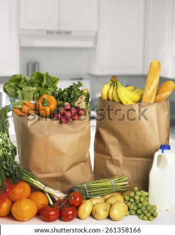 Assorted fruits and vegetables in brown grocery bag - stock photo