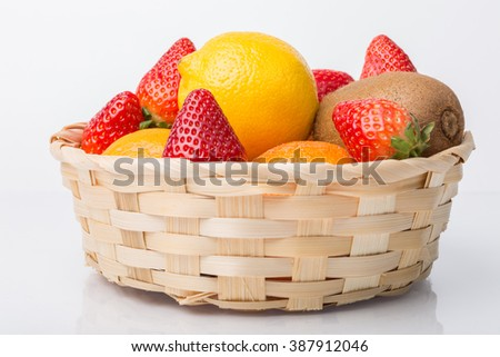 Assorted fruits in wicker basket isolated on white - stock photo