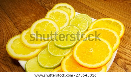 Assorted fruits on saucer on a wooden background - stock photo