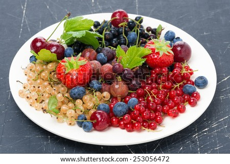 assorted garden berries on a plate on dark background, horizontal - stock photo