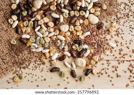 Assorted garden seeds scattered over burlap on rustic wood background.  Seeds include various beans, peas, corn, radishes, and carrots. - stock photo