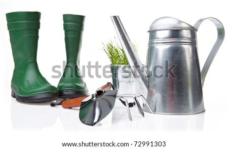 Assorted gardening supplies including watering can, pots, spade, shovel and cultivator on a white background - stock photo