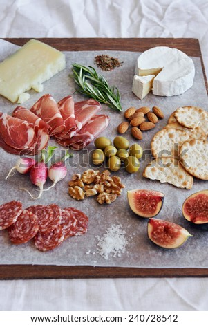 Assorted gourmet cured meat charcuterie salami, coppa, with brie camembert gruyere cheese served with olives nuts crackers and fruit - stock photo