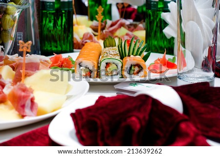 Assorted gourmet sushi rolls on a buffet with fish, smoked salmon and seaweed making colorful patterns at a party or celebration - stock photo