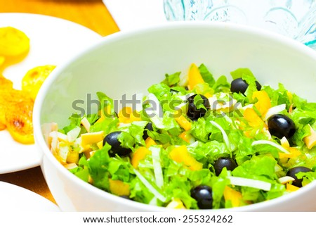 Assorted green leaf lettuce with squid and black olives - stock photo