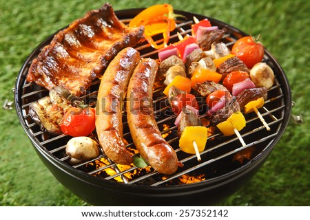Assorted grilled meat on a summer barbecue with sausages, spicy ribs and beef kebabs with vegetables, outdoors on a green lawn - stock photo
