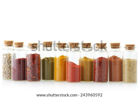 Assorted ground spices in bottles isolated on white background. - stock photo