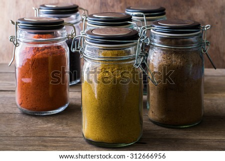 Assorted ground spices in bottles on wood, Still life with spices on wood table
