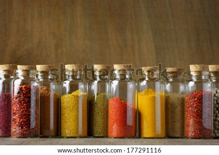 Assorted ground spices in bottles on wooden background. - stock photo