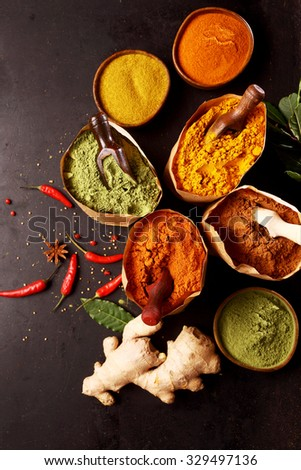 Assorted herbs, fresh and dried ground spices arranged on a dark metal background with hot chili peppers, root ginger, star anise and ground cayenne, curry, turmeric, matcha and ginger in paper bags - stock photo
