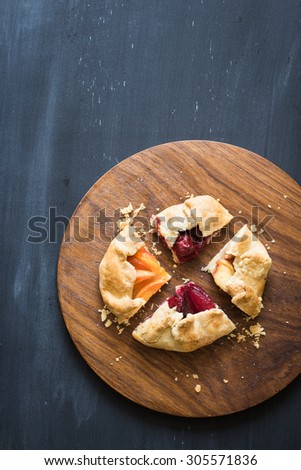 Assorted homemade pie pieces with pluots, apricots, sour cherries and peaches on the wooden cutting board. Chalkboard background with copy space. - stock photo