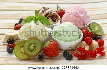 Assorted ice cream strawberry, banana, mint, chocolate and fresh berries on the wooden table - stock photo