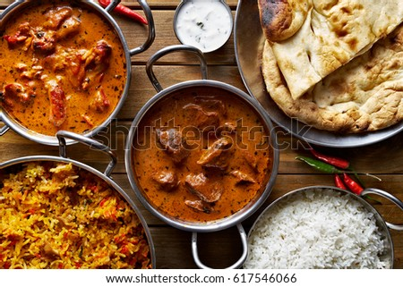 assorted indian curry and rice dishes shot from overhead composition