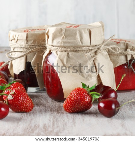 Assorted jams in glass jars and fresh berries on rustic wooden background. - stock photo