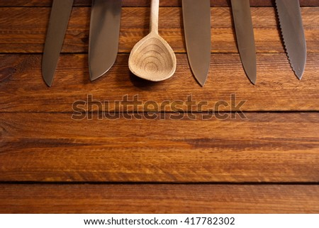 assorted knifes and wooden spoon on raw wooden table - stock photo