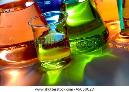 Assorted laboratory glass conical Erlenmeyer flasks and beaker flasks filled with liquid for an experiment in a science research lab