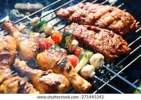 Assorted meat from chicken and pork and various vegetables on barbecue grill cooked for summer family dinner - stock photo