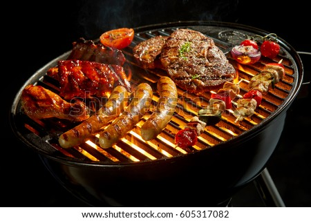 Assorted meat grilling over the hot fire on a portable barbecue with steak, sausage, kebabs, chicken , spare ribs and tomato