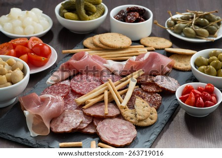 Assorted meat snacks and pickles on a blackboard, horizontal - stock photo