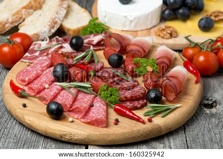 Assorted meats and sausages on a wooden board, horizontal - stock photo